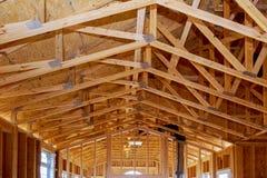 A vara nova do close-up construiu em casa sob a construção sob o quadro de madeira de quadro da estrutura do céu azul de casas de fotografia de stock