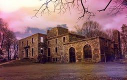Vara spökskrivare huset nedanför trädfilialer och purpurfärgad himmel arkivfoto