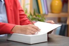 Vara upphovsman till den undertecknande autografen i bok på tabellen inomhus, closeupen royaltyfria bilder