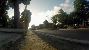 VARADERO, CUBA - DECEMBER 23, 2011: Cars driving on a street. At the evening stock footage