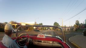 VARADERO, CUBA - DECEMBER 23, 2011: Convertible taxi driving stock footage