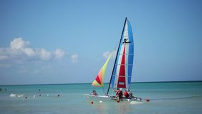 VARADERO, CUBA - DECEMBER 24, 2011: People on sailing catamaran. At the beach stock video