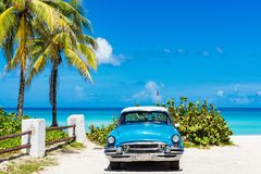 American blue 1955 classic car with a white roof parked direct on the beach in Varadero Cuba. American blue Ford Fairlane classic car parked on the beach in stock photos