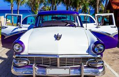 American blue white 1956 vintage car parked direct on the beach in Havana Cuba - Serie Cuba. American blue white Ford Fairlane vintage car parked on the beach in stock photography