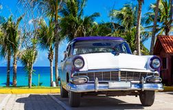 American blue white 1956 vintage car parked direct on the beach in Havana Cuba - Serie Cuba. HDR - American blue Ford Fairlane classic car parked on the Malecon royalty free stock image