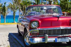 American red convertible 1956 vintage car parked direct on the beach in Havana Cuba - Serie. American blue white Ford Fairlane vintage car parked on the beach in stock images