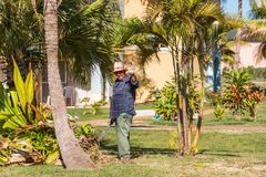 VARADERO, MATANZAS, CUBA - MAY 18, 2017: Cuban gardener on the background of the garden. Copy space for text. Royalty Free Stock Photography