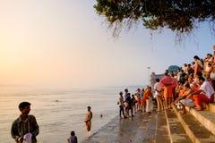 Varanasi, Índia - 10 de setembro de 2018: ancião que executa o ritual diário do puja na água calma de Ganges River no nascer do s foto de stock