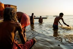 Varanasi, Índia - 10 de setembro de 2018: ancião que executa o ritual diário do puja na água calma de Ganges River no nascer do s imagens de stock