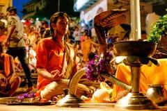 Varanasi, Índia - 16 de setembro de 2018: próximo acima do padre hindu novo que reza na cerimônia ritual diária do aarti do ganga imagens de stock