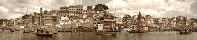 Varanasi, Índia - em novembro de 2009: Barcos com os turistas e os locals que flutuam ao longo da terraplenagem, dos ghats e das  Fotografia de Stock Royalty Free