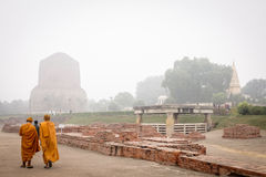 VARANASI, INDIA - DECEMBER 2, 2016: Buddhist monks and tourists come to visit and pray in the misty morning at Dhamekh Stupa. Stock Photos