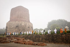 VARANASI, INDIA - DECEMBER 2, 2016: De boeddhistische monniken en de toeristen komen in de nevelige ochtend in Dhamekh Stupa bezo Stock Fotografie