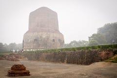 VARANASI, INDIA - DECEMBER 2, 2016: De boeddhistische monniken en de toeristen komen in de nevelige ochtend in Dhamekh Stupa bezo Stock Foto