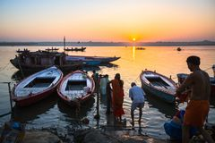 Dawn on the Ganges river, with the silhouettes of boats with pilgrims. stock image