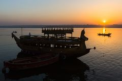 Dawn on Ganges river, with silhouettes of boats with pilgrims. VARANASI, INDIA - MAR 18, 2018: Dawn on Ganges river, with silhouettes of boats with pilgrims royalty free stock photo