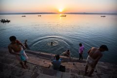 Dawn on Ganges river, with silhouettes of boats with pilgrims. stock photos
