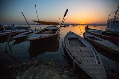 Dawn on Ganges river, with silhouettes of boats with pilgrims. VARANASI, INDIA - MAR 18, 2018: Dawn on Ganges river, with silhouettes of boats with pilgrims royalty free stock photos