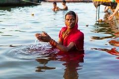 Varanasi, India, 27 Mar 2019 - Hindu woman in sari making offering to the gods in Ganga river at Varanasi, India royalty free stock photos