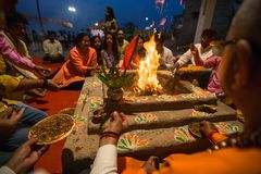 People sit near a ceremonial fire near the Holy Ganges at night. VARANASI, INDIA - MAR 22, 2018: People sit near a ceremonial fire near the Holy Ganges at night royalty free stock image