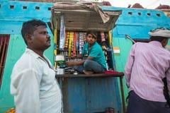 Street seller on the banks of the sacred Ganges river selling selling milk tea - masala. VARANASI, INDIA - MAR 17, 2018: Street seller on the banks of the stock image