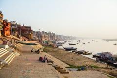 View from a boat glides through water on Ganges river along shore of Varanasi. VARANASI, INDIA - MAR 26, 2018: View from a boat glides through water on Ganges royalty free stock photo