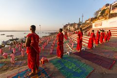 Young hindu monks conduct a ceremony to meet the dawn on the banks of the Ganges, and raise the Indian flag. VARANASI, INDIA - MAR 18, 2018: Young hindu monks stock photos