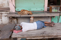 Man and dog take a nap in front of store Stock Photos