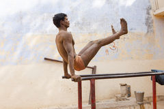 Young wrestler stretching on parallel bars Royalty Free Stock Photo