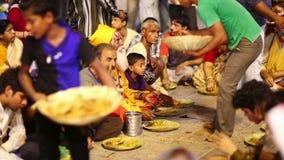 VARANASI, INDIA - MAY 2013: people eating free food at street stock footage