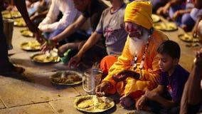 VARANASI, INDIA - MAY 2013: people eating free food at street stock video