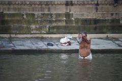 Varanasi, India, 26 November, 2017: Een mens die op de Gange-rivier bidden Royalty-vrije Stock Afbeeldingen