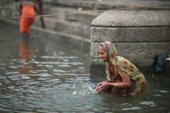 Varanasi, India, 26 November, 2017: Een vrouw die op Gange bidden Stock Foto's