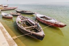 VARANASI, INDIA - OCTOBER 25, 2016: Small boats at Ghats riverfront steps leading to the banks of the River Ganges in. Varanasi, India royalty free stock photography