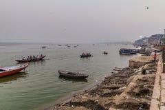 VARANASI, INDIA - OCTOBER 25, 2016: Small boats near Ghats riverfront steps leading to the banks of the River Ganges in. Varanasi, India royalty free stock photos