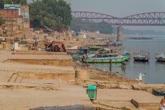 VARANASI, INDIA - OCTOBER 25, 2016: View of a Ghat riverfront steps of sacred river Ganges in Varanasi, India. Malviya. Bridge in the background stock photo