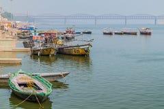 VARANASI, INDIA - OCTOBER 25, 2016: Wooden boats at sacred river Ganges in Varanasi, India. Malviya Bridge in the. Background stock images