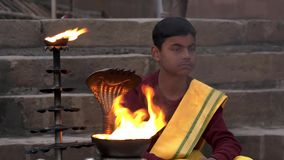 Varanasi, india, young monk and sacred fire. Portrait of a young religious man sitting near a sacred fire stock footage