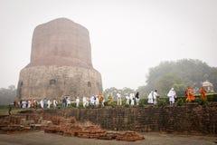 VARANASI INDIEN - DECEMBER 2, 2016: Buddistiska munkar och turister kommer att besöka och be i den dimmiga morgonen på Dhamekh St Arkivbild