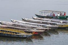 VARANASI, INDIEN - 26. JANUAR 2012: Alte Boote auf braunem Wasser von Stockbilder
