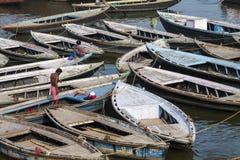 VARANASI, INDIEN - 26. JANUAR 2012: Alte Boote auf braunem Wasser von Stockfoto