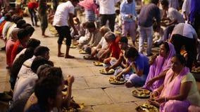 VARANASI, INDIEN - MAI 2013: Leute, die freies Lebensmittel an der Straße essen stock video
