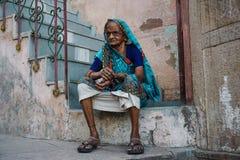Varanasi INDIEN - MAJ 29, 2017: Gammal indisk kvinna som sitter på trappan royaltyfria foton