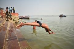 Varanasi Indien, November 26, 2017: Youn manbanhoppning i Gangen royaltyfria bilder