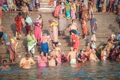 VARANASI INDIEN - OKTOBER 23: Det hinduiska folket tar ett bad i rien royaltyfri bild