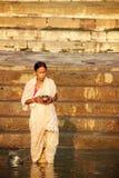 VARANASI INDIEN - OKTOBER 23: En kvinnahållbehållare och ber och Arkivbilder