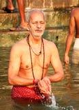 VARANASI INDIEN - OKTOBER 23: En man ber och tillber till guden på gummin Fotografering för Bildbyråer