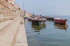 VARANASI, INDIEN - 25. OKTOBER 2016: Kleine Boote an den Ghats-Flussuferschritten, die herein zu die Banken des Flusses der Gange stockfotografie