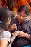 Varanasi, la India - 24 de julio de 2011: Tatuaje de la alheña a mano por el artista de maquillaje Fotos de archivo