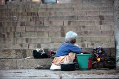 Varanasi. MP116: A poor old homeless woman cooks food on the ghats at Varanasi, Uttar Pradesh, India Stock Image